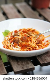A plate of spaghetti with meat sauce in a large white bowl. Atop of the spaghetti are three meatballs which have been made with insect burger patties made with mealworms.