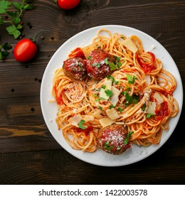 Plate of spaghetti with meatballs, parmesan and tomato sauce on a rustic wooden table. Tasty Italian pasta food. Top view shot directly above.