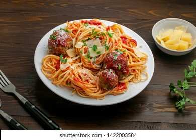 Plate of spaghetti with meatballs, parmesan and tomato sauce on a rustic wooden table. Tasty Italian pasta food.