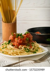A plate of spaghetti with meatballs in tomato sauce and raw spaghetti vertical shot with copy space/