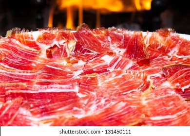 plate of Spanish jamon iberico slices (serrano ham) with a fireplace as background