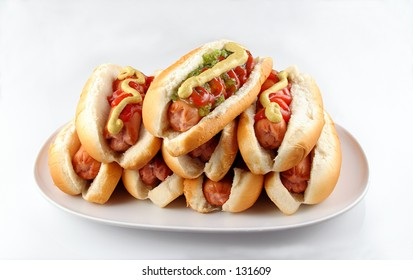 Plate of stacked hotdogs.  Ketchup, mustard, and relish.