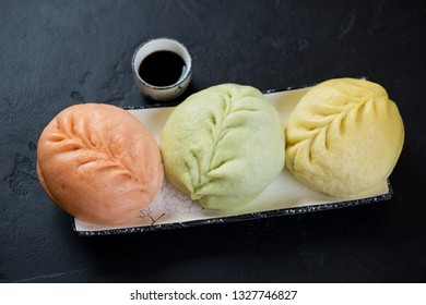 Plate with steamed korean pjan-se or pigodi buns of different colors, elevated view on a black stone background