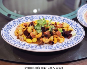 Plate of stir fried ham, chicken, shirmp, chinese date, gingko, chestnut,  waternut and cashew nut with oyster sauce place on lazy susan table. Traditional Chinese food with selective focus.