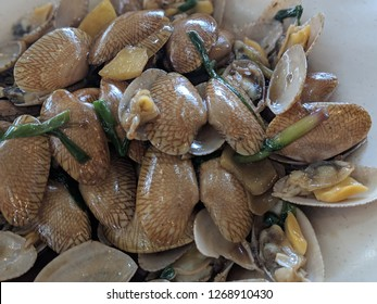 plate of stir fried saltwater clams with ginger and green onions in sauce beautifully plated
