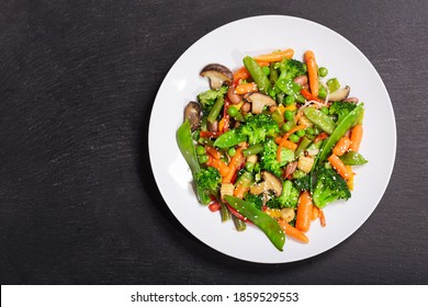 plate of stir fried vegetables on dark background, top view