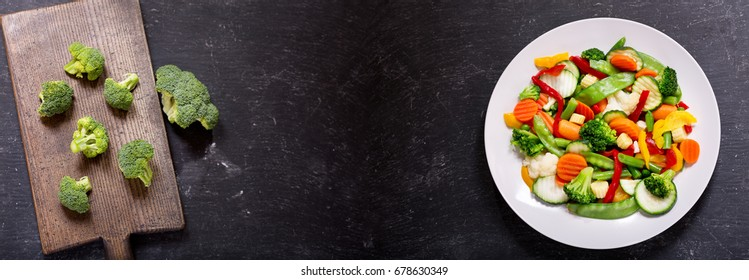 plate of stir fry vegetables on a dark background, top view