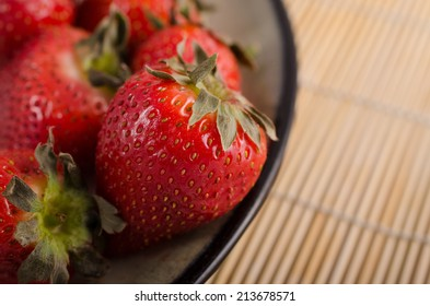 Plate of strawberries in 2/3 frame on bamboo place-mat.