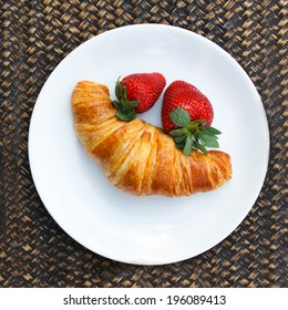 Plate with strawberries and croissant against wooden background