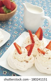 A plate of strawberry meringue nests with fresh cream and chocolate