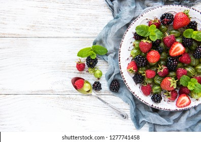 Plate with summer berries on a old wooden table