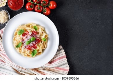 Plate with tagliatelle pasta and napkin on a dark background. Cherry tomatoes, basil, garlic and parmesan. Ingredients for pasta. Flat lay.