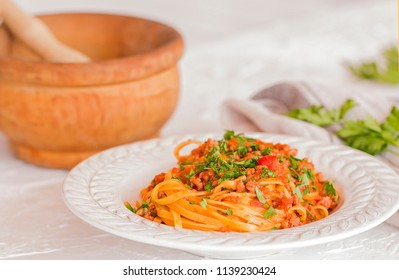 A plate of Tagliatelle with ragu sauce. Background: a wooden pestle.