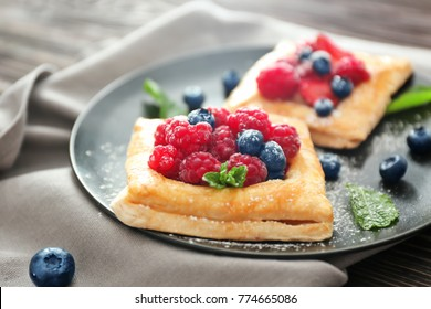 Plate with tasty berry pastries on table