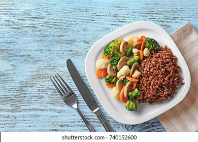 Plate with tasty brown rice and vegetables on wooden table
