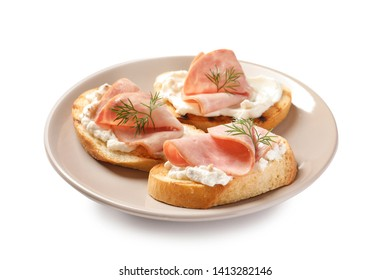 Plate of tasty bruschettas with ham on white background