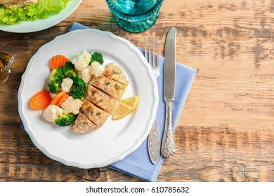 Plate with tasty chicken breast on table