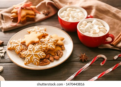 Plate with tasty Christmas cookies and cups of hot chocolate on wooden background