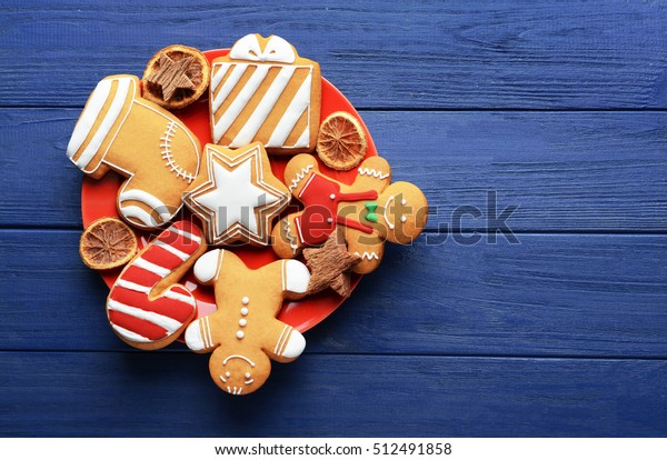 Plate with tasty Christmas cookies on wooden table