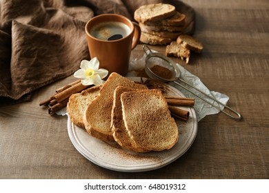 Plate with tasty cinnamon toasts on wooden table