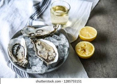 Plate with tasty cold oysters on table