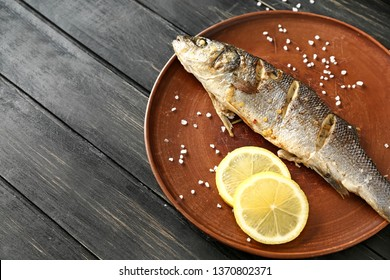 Plate with tasty cooked fish on wooden table