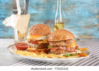 Plate with tasty double burgers on table against wall background
