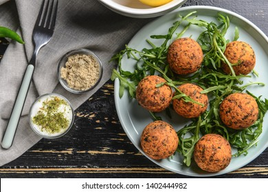 Plate with tasty falafel balls on wooden table