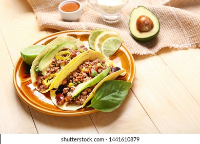 Plate with tasty fresh tacos on wooden background