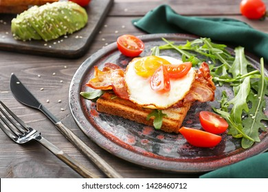 Plate with tasty grilled bread, fried egg and bacon on wooden table