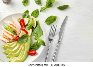 Plate with tasty grilled chicken fillet and vegetables on white wooden table