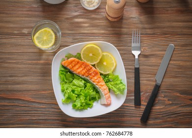 Plate with tasty grilled salmon and lemon slices on table