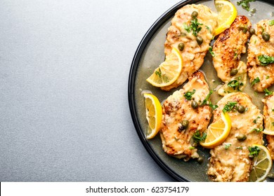 Plate with tasty Italian chicken piccata on table