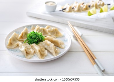 Plate with tasty Japanese gyoza on white table