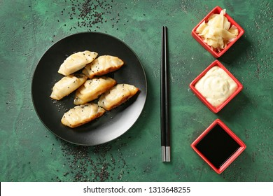 Plate with tasty Japanese gyoza and sauces on color background