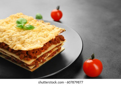 Plate with tasty lasagna on gray background