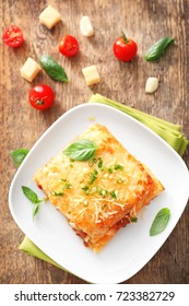 Plate with tasty lasagna on wooden background