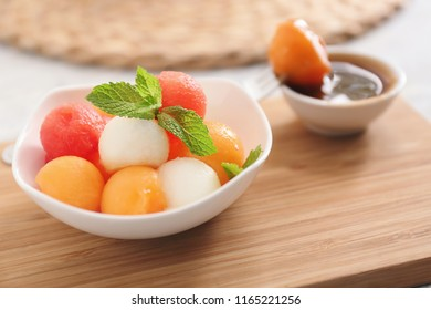 Plate with tasty melon dessert on wooden board