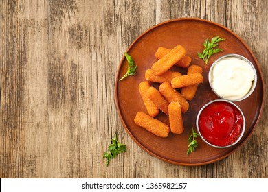 Plate with tasty mozzarella sticks and sauces on wooden table