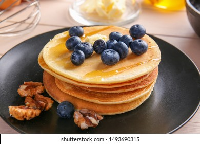 Plate with tasty pancakes on wooden background