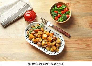 Plate with tasty potato wedges and tomato sauce on table