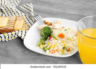Plate with tasty rice, meat and vegetables near glass of juice on table