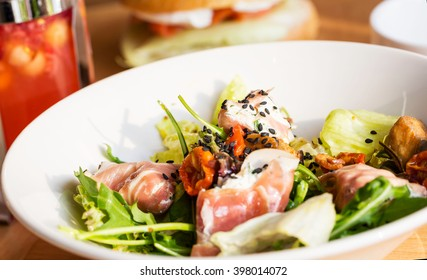 plate of tasty salad with   sun-dried cherry tomatoes, arugula, prosciutto, sprinkled with sesame seeds