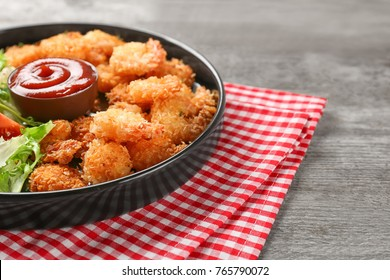 Plate with tasty shrimp basket and sauce on table