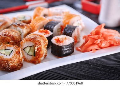 Plate with tasty sushi rolls on table, closeup