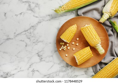 Plate with tasty sweet corn cobs on marble table, top view