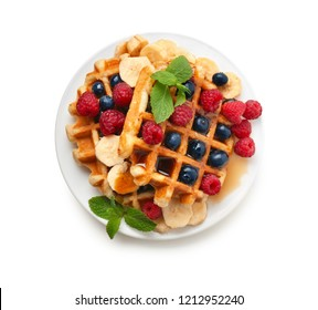Plate with tasty waffles, fruit and berries on white background