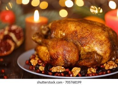 Plate with tasty whole roasted turkey on table against defocused lights