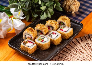 Plate of tempura maki sushi rolls with cream cheese, avocado and tuna at decorated with flowers table background.