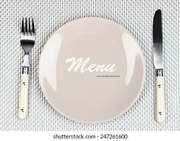 """Plate with text """"Menu"""", fork and knife on tablecloth background"""